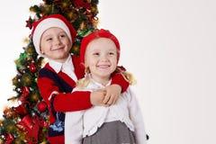 Soeur et frère étreignant sous l'arbre de Noël Images libres de droits