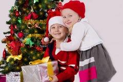 Soeur et frère étreignant sous l'arbre de Noël Photos stock