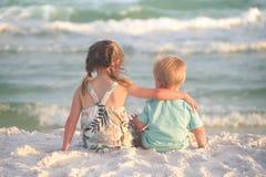 Soeur et frère étreignant sur la plage Photo libre de droits