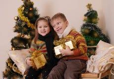 Soeur et frère ayant l'amusement sous l'arbre de Noël d'or Image stock