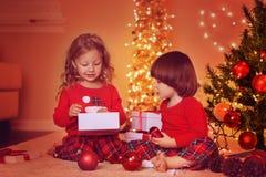 Soeur et frère déballant des cadeaux de Noël Photo libre de droits