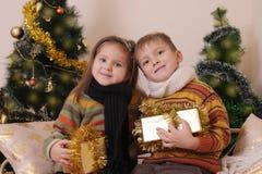 Soeur et frère dans des vêtements tricotés avec des présents sous d'or Images libres de droits