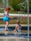 Soeur et frère dans une fontaine de ville Photos libres de droits