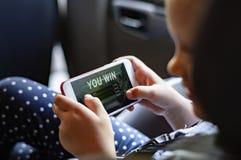 Soeur et frère jouant avec les dispositifs numériques dans la voiture image stock