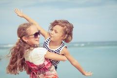 Soeur et frère jouant sur la plage au temps de jour Images libres de droits