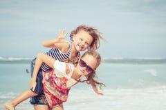 Soeur et frère jouant sur la plage au temps de jour Photos libres de droits