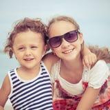 Soeur et frère jouant sur la plage au temps de jour Image stock