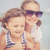 Soeur et frère jouant sur la plage au temps de jour Images stock