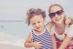 Soeur et frère jouant sur la plage au temps de jour Photographie stock libre de droits