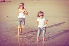 Soeur et frère jouant sur la plage au temps de jour Photographie stock