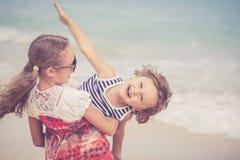 Soeur et frère jouant sur la plage au temps de jour Image libre de droits