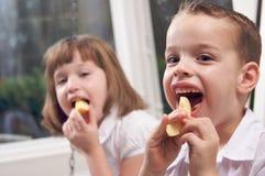 Soeur et frère mangeant un Apple Image libre de droits