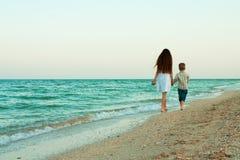 Soeur et frère marchant loin par la plage de soirée Image stock