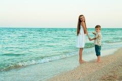 Soeur et frère marchant loin par la plage de soirée Images libres de droits