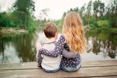 Soeur et frère s'asseyant et appréciant sur le pont en bois Photos stock