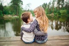 Soeur et frère s'asseyant et appréciant sur le pont en bois Photo stock