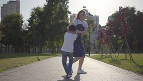 Soeur plus âgée joyeuse tournant autour avec le jeune frère tenant des mains en parc d'été r amical clips vidéos