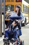 Soeur poussant le frère handicapé dans le fauteuil roulant Photographie stock