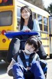 Soeur poussant le frère handicapé dans le fauteuil roulant Images libres de droits