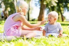 Soeur soigneuse alimentant son frère en parc images stock