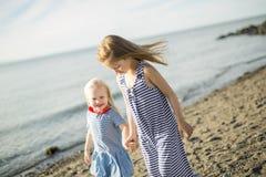 Soeurs à la plage sur le coucher du soleil Images libres de droits
