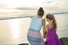 Soeurs à la plage sur le coucher du soleil Image libre de droits