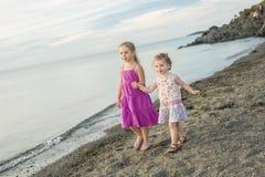 Soeurs à la plage sur le coucher du soleil Photographie stock