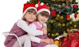 Soeurs étreignant dans le traîneau sous l'arbre de Noël Photos libres de droits