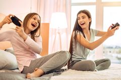 Soeurs adolescentes optimistes jouant des jeux vidéo avec émotion Photographie stock