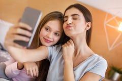 Soeurs adorables prenant des selfies dans la chambre à coucher Image stock