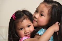 Soeurs asiatiques étreignant et souriant à l'intérieur Images libres de droits