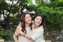 Soeurs asiatiques étreignant et souriant en parc Images stock