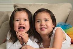 Soeurs asiatiques Biracial d'enfant en bas âge s'étendant sur l'estomac souriant à l'appareil-photo Image libre de droits