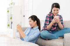 Soeurs attirantes heureuses détendant dans le salon Image stock