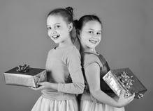 Soeurs avec les boîte-cadeau enveloppés pour des vacances Les enfants ouvrent des cadeaux pour Noël Filles avec les visages de so photographie stock libre de droits