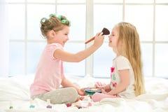 Soeurs de filles de petits enfants faisant le maquillage à l'intérieur Image libre de droits