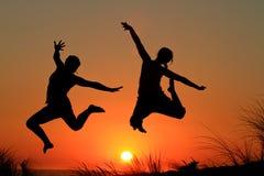 Soeurs de saut de coucher du soleil Photographie stock