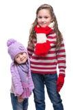 Soeurs de sourire mignonnes portant le chandail, l'écharpe, le chapeau coloré et les gants tricotés d'isolement sur le fond blanc Photographie stock