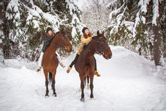 Soeurs et cheval jumeaux dans la forêt d'hiver Photographie stock libre de droits
