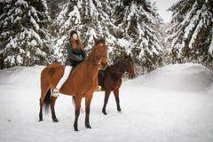 Soeurs et cheval jumeaux dans la forêt d'hiver Image stock