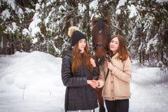 Soeurs et cheval jumeaux dans la forêt d'hiver Photographie stock