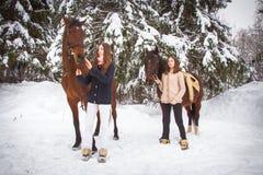 Soeurs et cheval jumeaux dans la forêt d'hiver Image libre de droits