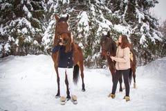 Soeurs et cheval jumeaux dans la forêt d'hiver Images stock