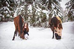 Soeurs et cheval jumeaux dans la forêt d'hiver Photo stock