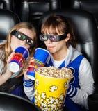 Soeurs heureuses ayant des casse-croûte dans la salle de cinéma 3D Photographie stock libre de droits