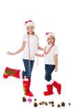 Soeurs heureuses dans les chapeaux de Santa et les chaussettes de cadeau Image libre de droits