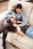 Soeurs heureuses et riantes dans le salon Photographie stock libre de droits