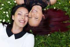 Soeurs heureuses se trouvant sur l'herbe dehors Photos stock