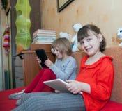 Soeurs jouant des jeux sur des comprimés chez la pièce du ` s des enfants Images stock