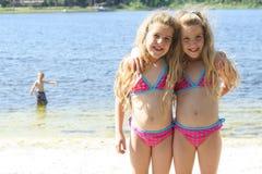 Soeurs jumelles dans des maillots de bain au lac photo stock